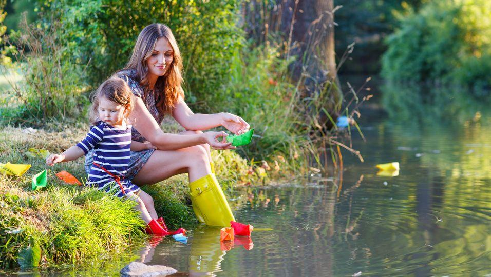 Frau in Gummistiefeln lässt mit ihrer Tochter Papierschiffchen schwimmen