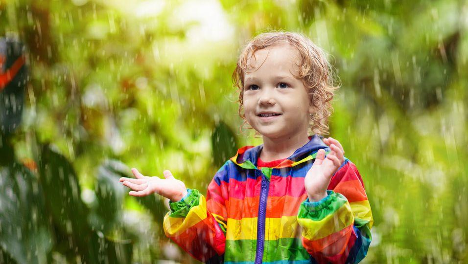 Kleiner Junge spielt im Regen