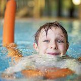 Junge lernt schwimmen