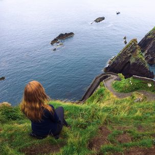 Kind blickt auf irische Küstenlandschaft