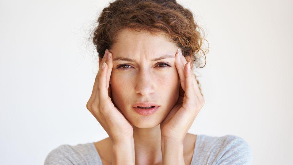 Frau mit Kopfweh massiert sich die Schläfen