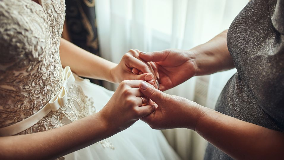 Mutter oder Großmutter hält die Hände der Braut