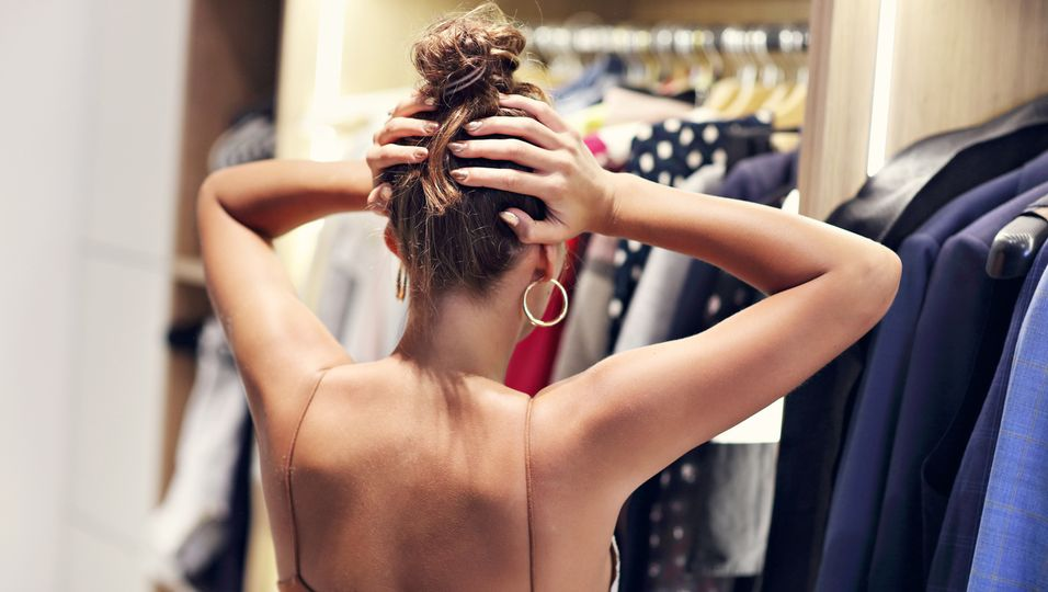 Frau steht verzweifelt vor übervollem Kleiderschrank
