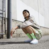Eine Frau hockt  vor einem Gebäude und trägt besondere Sneaker.