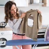 Frau hält Kleidungsstück mit Brandloch