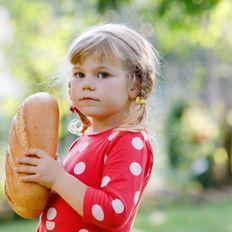 Mädchen freut sich über einen Brotlaib
