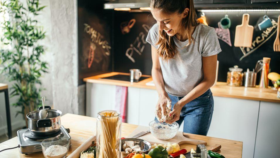 Frau, die an einer Kücheninsel steht und Zutaten vorbereitet