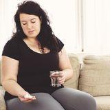 Übergewichtige Frau mit Pillen