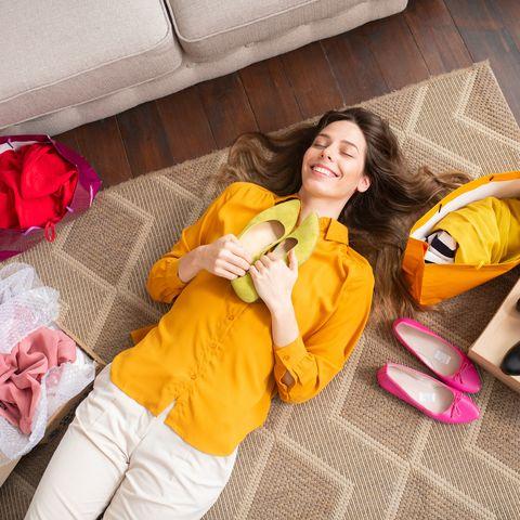 Frau, die auf dem Boden liegt und ein Paar Schuhe in den Händen hält.