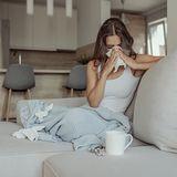 Erkältete Frau sitzt auf einem Sofa und putzt sich die Nase