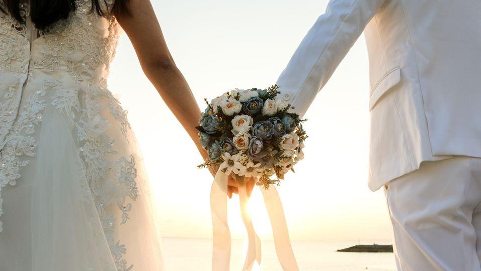 Hochzeit, Frau und Mann halten Blumenstrauß