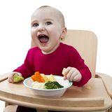 Baby isst feste Nahrung im Hochstuhl und lacht
