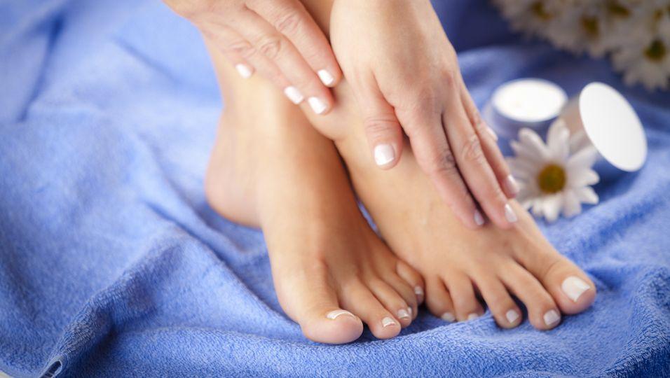 Frau massiert sich Füße auf blauem Handtuch
