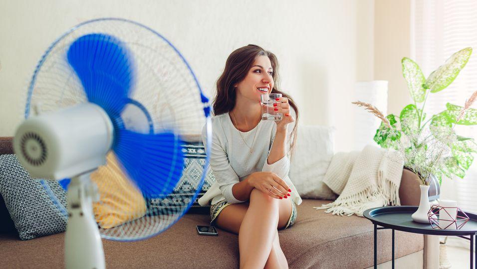 Frau kühlt sich mit Ventilator