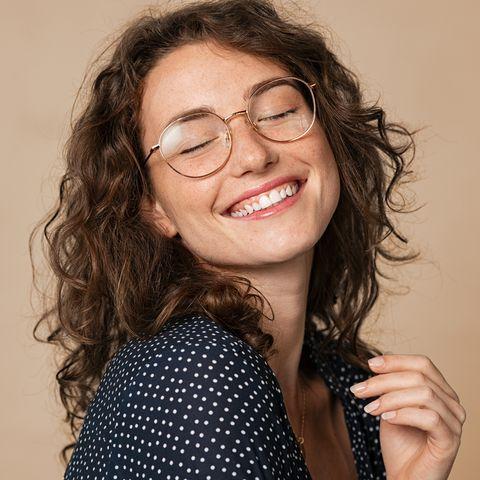 Frau mit braunen Locken, die offen lacht.