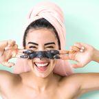 Eine Frau macht sich eine Gesichtsmaske.