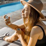 Frau verwendet Gesichtsspray in der Sonne