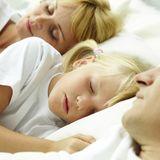 Kind schläft im Bett der Eltern