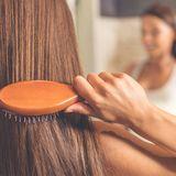 Frau bürstet lange Haare