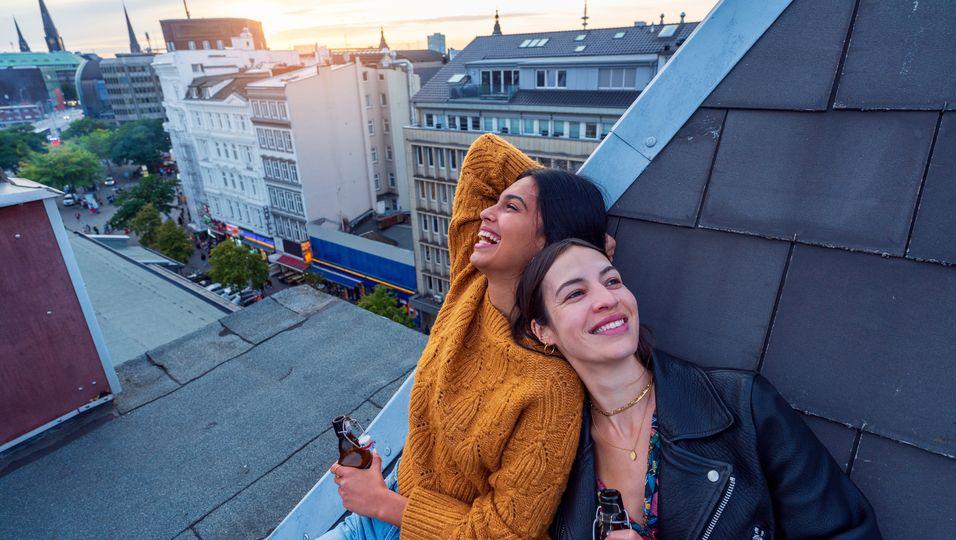 Zwei Frauen mit Bierflaschen, die auf einem Dach sitzen und an einer Schräge lehnen.