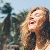 Frau streckt Gesicht in die Sonne