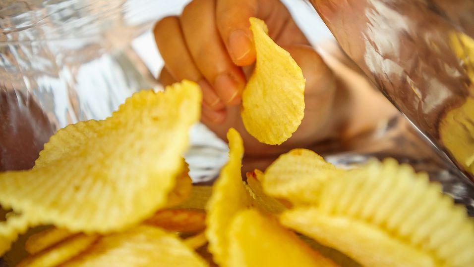Hand greift nach Chips