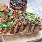 Gegrilltes Fleisch mit Schnittlauch auf Holzbrett