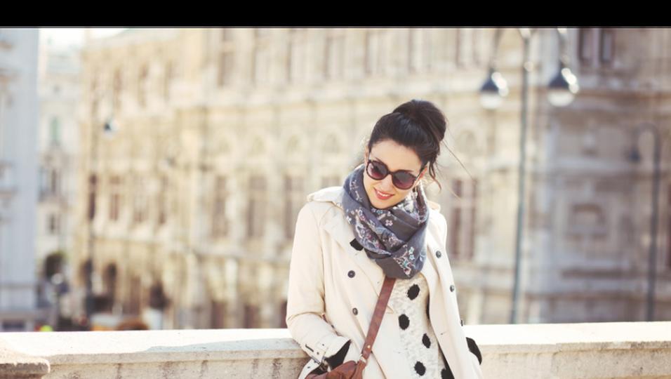 Frau mit Schal und Sonnenbrille lehnt an Brückengeländer