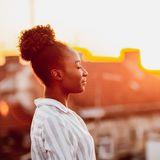 Frau auf einem Dach vor Sonnenuntergang, die tief einatmet.