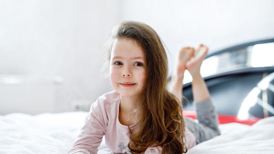 Mädchen mit langen Haaren liegt auf dem Bett