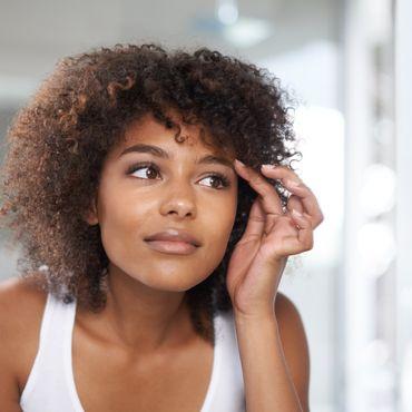 Frau guckt Brauen im Spiegel an