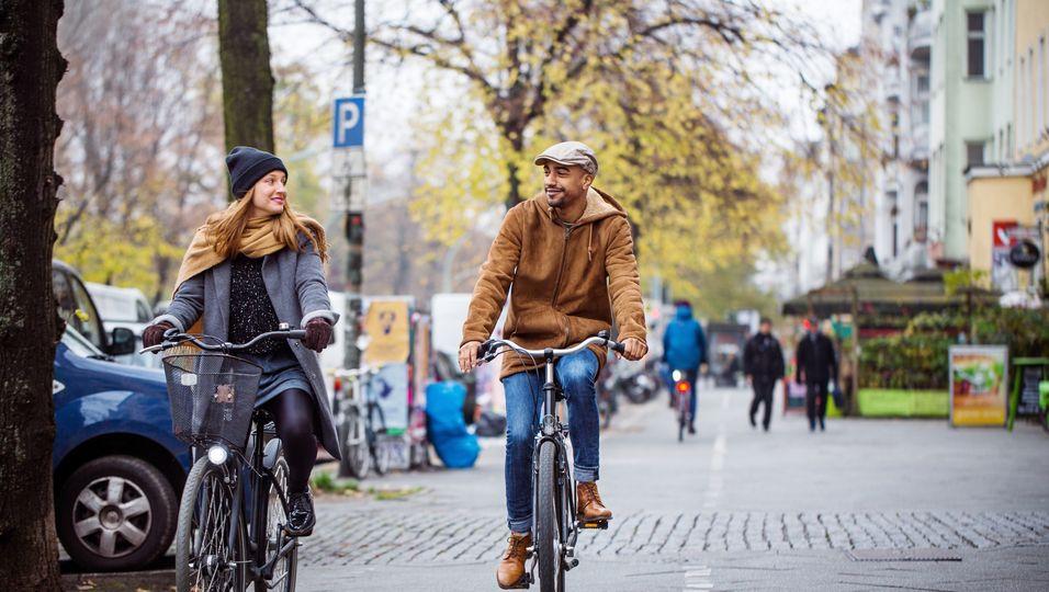 Frau und Mann, die auf einem Fahrrad durch die Stadt fahren