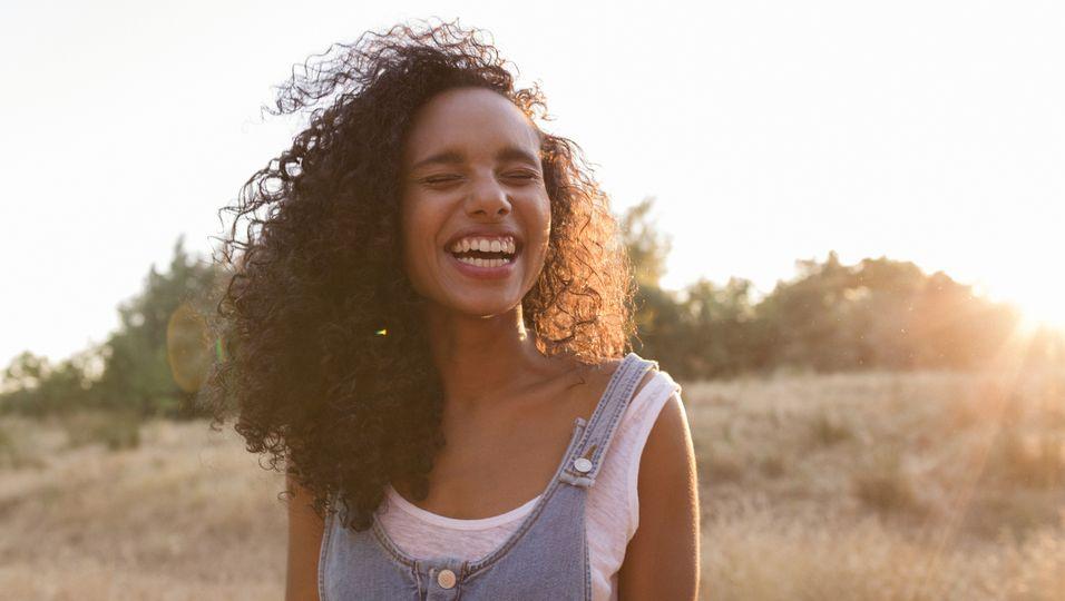 Frau lächelnd bei Sonnenuntergang