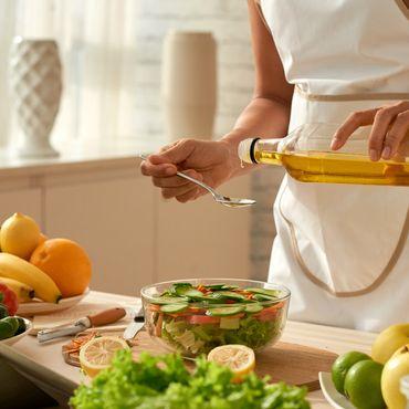 Frau gibt Olivenöl zum Salat