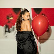 Rihanna in einem schwarzen Kleid und mit rotem Luftballon.