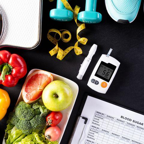 Waage, Obst, Gemüse, Sportschuhe, Blutzuckermessgerät, Tabelle und Maßband auf schwarzen Untergrund.