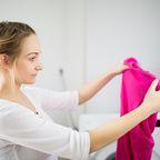 Frau blickt auf rosa Wäschstück