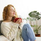 Entspannte junge Frau mit großer Tasse
