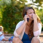 Gestresste, traurige Mutter vor einem Spielplatz