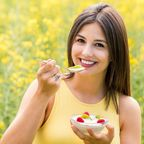 Junge Frau isst Obst mit Joghurt im Freien