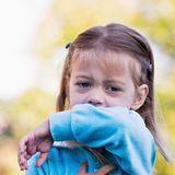 Mädchen hustet in ihre Armbeuge
