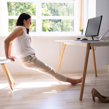 Frau macht Fitnessübungen am Bürostuhl
