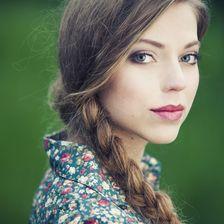 Eine Frau mit einer floralen Bluse uns einem seitlich geflochtenen Zopf.