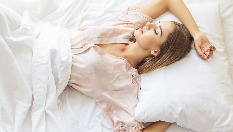 Frau räkelt sich in Bett