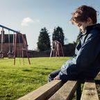 Einsamer Junge auf einer Bank