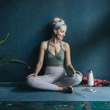 Frau auf Yogamatte vor blauer Wand