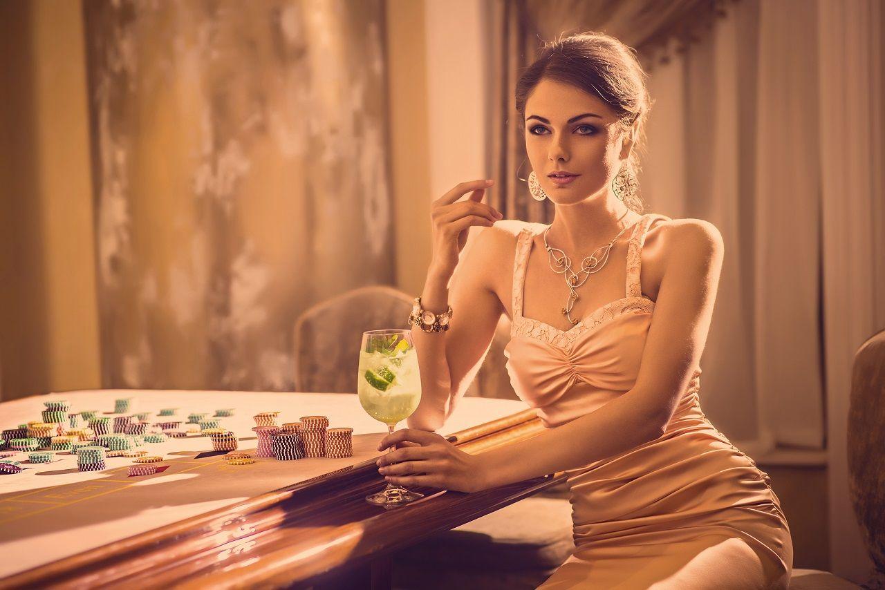 Frau mit Cocktail in rosefarbem Trägerkleid