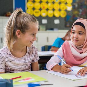 2 Mädchen unterhalten sich im Klassenzimmer