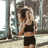 Frau in Laufshorts und Top, die in einem Wald am joggen ist.