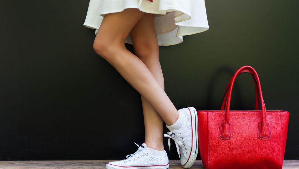 Frau im hellen Kleid mit Sneaker